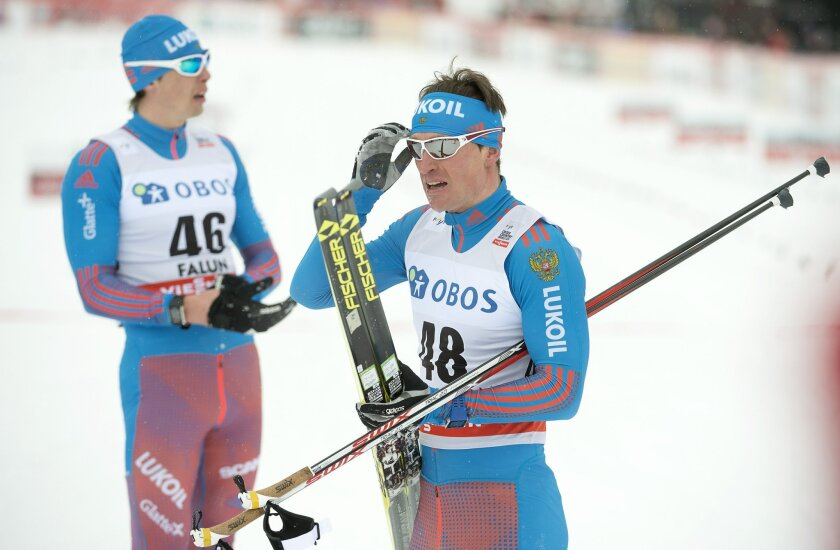 Russia's Maksim Vylegzjanin celebrates winning with second placed compatriot Aleksandr Bessmertnych, left, after the men's 10km competition at the FIS Cross-Country World Cup in Falun, Sweden, Saturday Feb. 13, 2016. (Maja Suslin/TT via AP) SWEDEN OUT