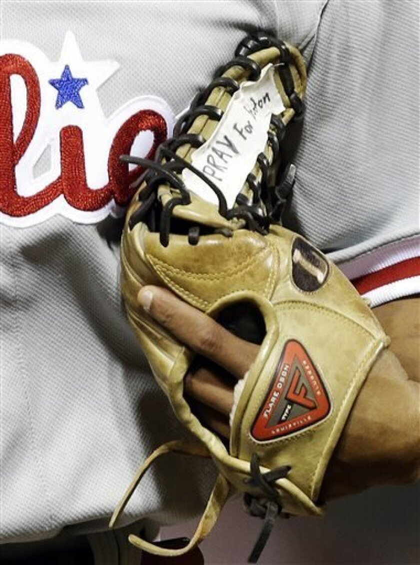Philadelphia Phillies center fielder Ben Revere runs off the field with tape on his glove that says 'Pray for Boston,' for the victims of the Monday bombings at the Boston Marathon, in the fifth inning of a baseball game against the Cincinnati Reds, Tuesday, April 16, 2013, in Cincinnati. (AP Photo
