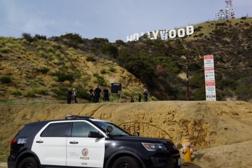 "A police car in front of the Hollywood sign, which reads ""Hollyboob"""