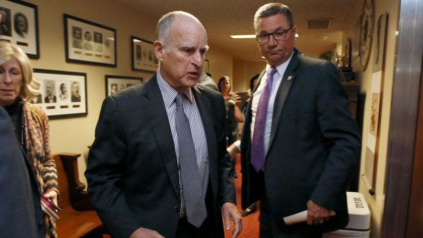Gov. Jerry Brown walks into a meeting of the Senate Democratic Caucus to urge them to approve a tran