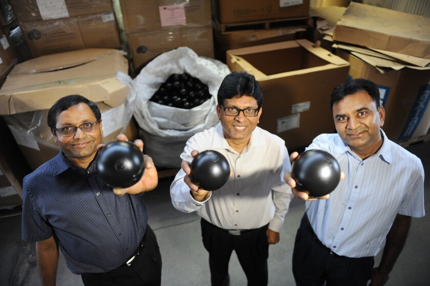 Business partners C.P. Kheni, left, Vasant Dobaria and Praful Bajaria of Artisan Screen Printing hold some of the 89.6 million black plastic shade balls manufactured at their plant in Azusa.