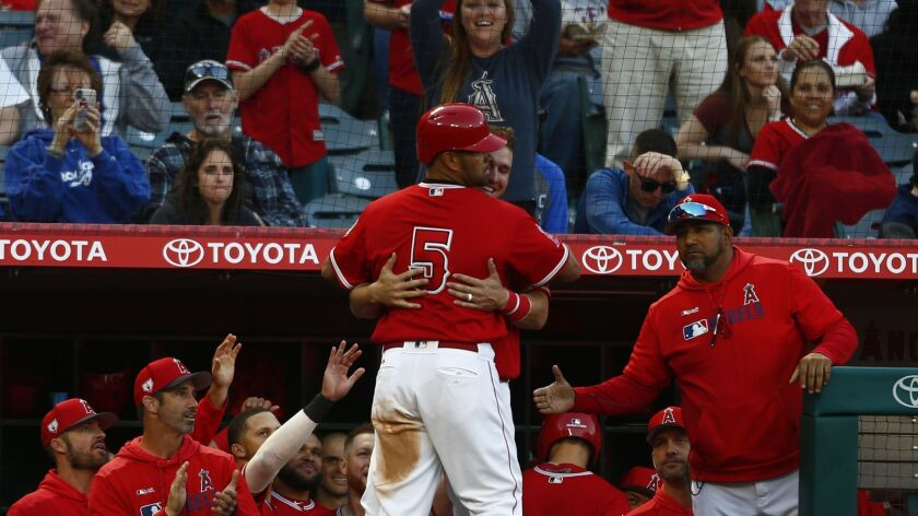 Angels' Albert Pujols (5) gets a hug from teammate Mike Trout (27) after hitting a two-run home run against the Dodgers in the fourth inning.