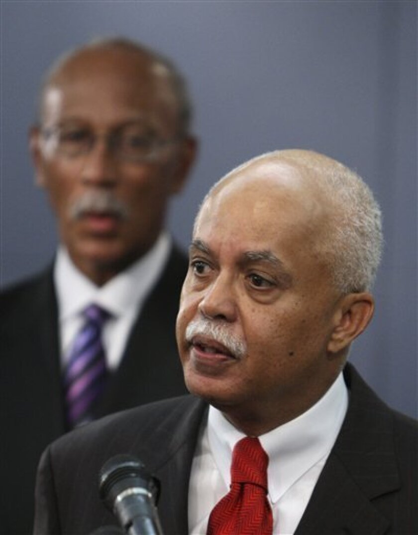 Detroit Police Chief Warren Evans, standing in front of Mayor Dave Bing, left, addresses the media in the mayor's office in Detroit on Monday, July 6, 2009. Evans will replace James Barren, who was fired Friday. Barren was brought out of retirement and appointed chief in September by then-Mayor Ken Cockrel Jr. after Ella Bully-Cummings retired. (AP Photo/Carlos Osorio)