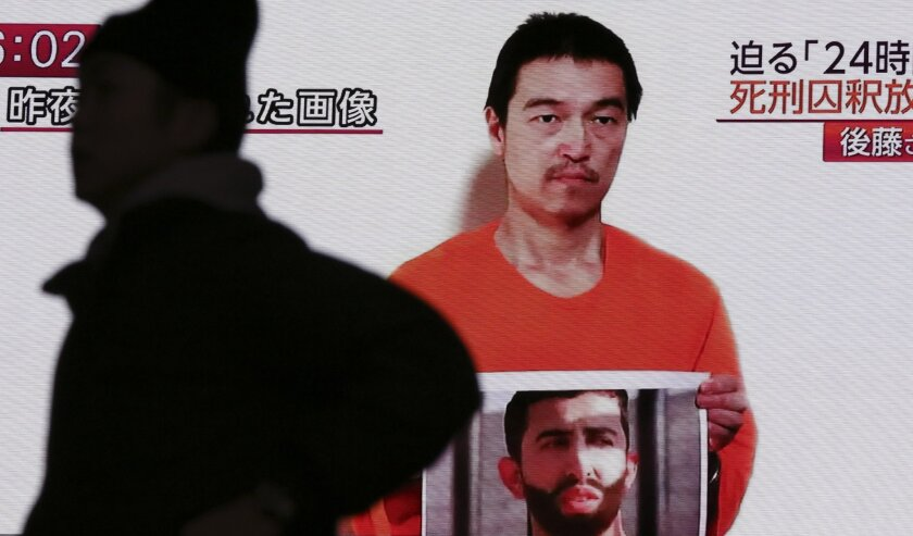 Japanese hostage Kenji Goto holds what appears to be a photo of Jordanian pilot Lt. Moaz Kasasbeh in a YouTube video projected on a big screen TV on Wednesday. The Islamic State hostage has reportedly been beheaded by his captors.