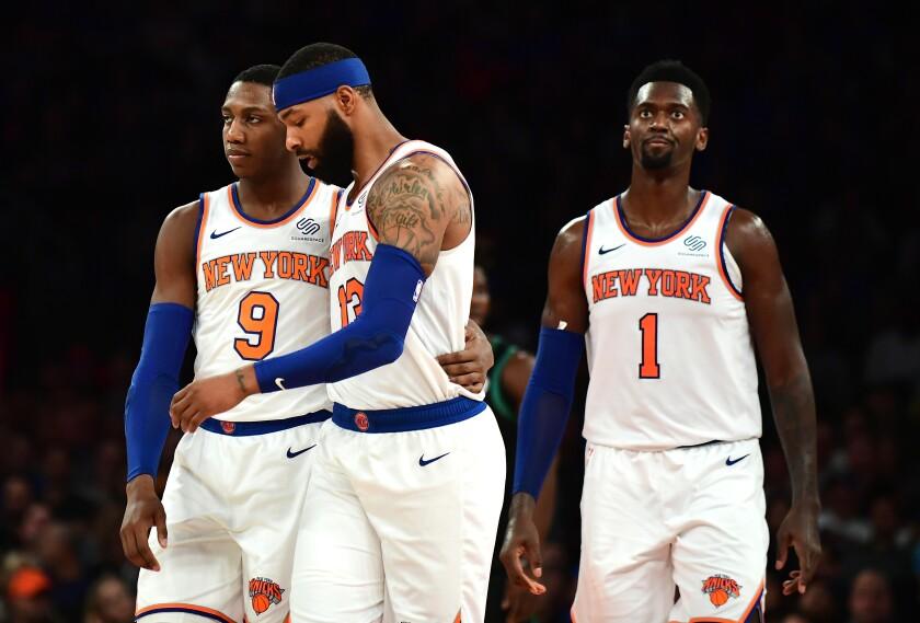 Knicks rookie RJ Barrett, left, hugs teammate Marcus Morris as Bobby Portis looks on during a loss to the Boston Celtics on Oct. 26.