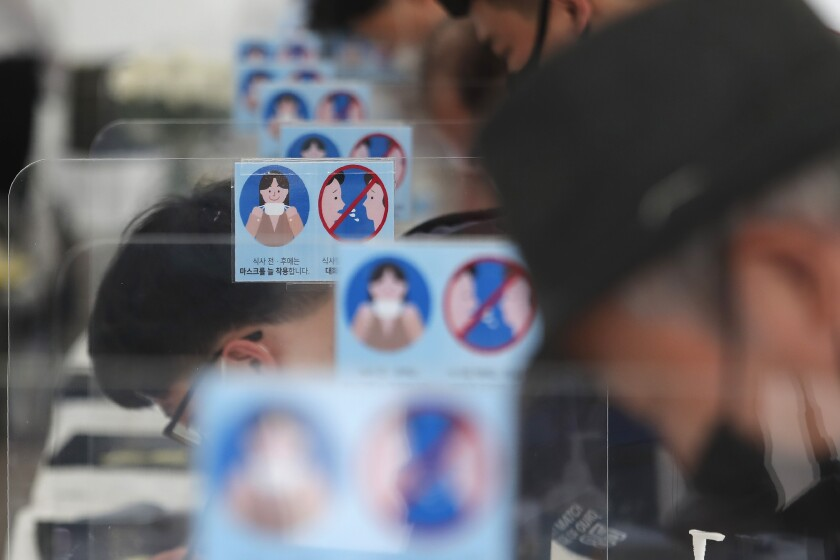 """Notices about precautions against new coronavirus are seen as mourners sign guestbooks at a memorial altar for late Seoul Mayor Park Won-soon at Seoul City Hall Plaza in Seoul, South Korea, Sunday, July 12, 2020. The sign on notices reads: """"Wearing A Mask."""" (AP Photo/Ahn Young-joon)"""