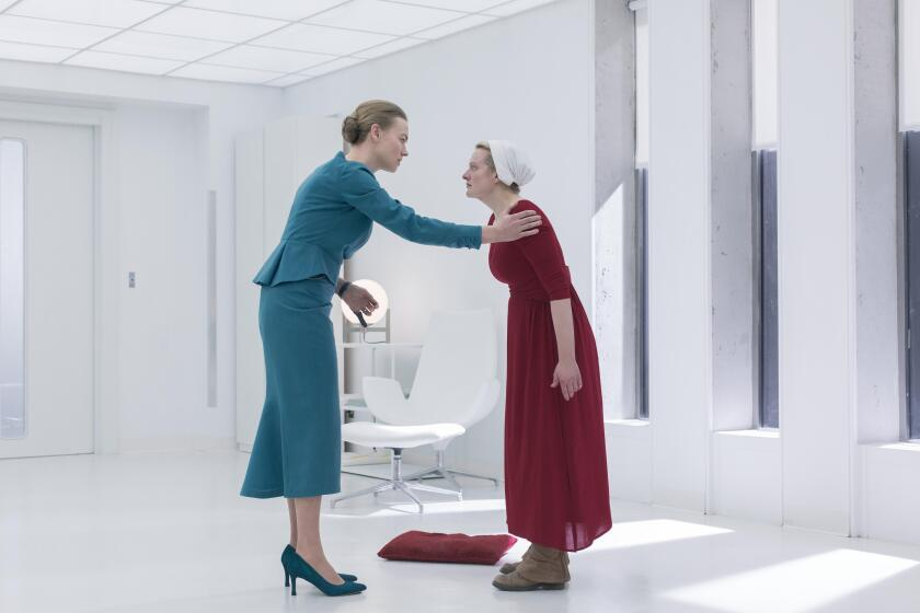"Yvonne Strahovski and Elisabeth Moss in a scene from Season 3 of ""The Handmaid's Tale."""