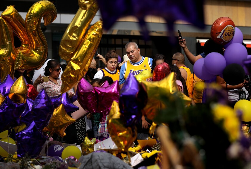 A man and woman in Lakers jerseys can be seen through purple and gold balloons among a crowd at L.A. Live.