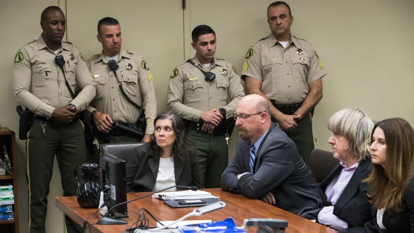 Louise Turpin, left, and David Turpin, second from right, pleaded not guilty to multiple counts of torture, child abuse, abuse of dependent adults and false imprisonment Thursday in Riverside County Superior Court.