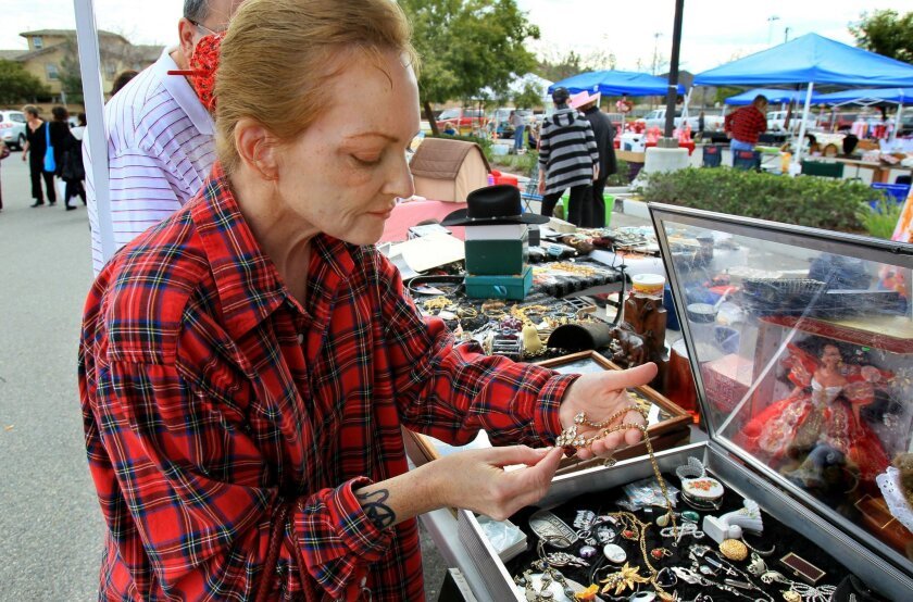 Customer Rhonda Favero inspects jewelry offered by seller Patricia Buckner, at right, Saturday at the Community Flea Market in the parking lot of the Murrieta Senior Center.