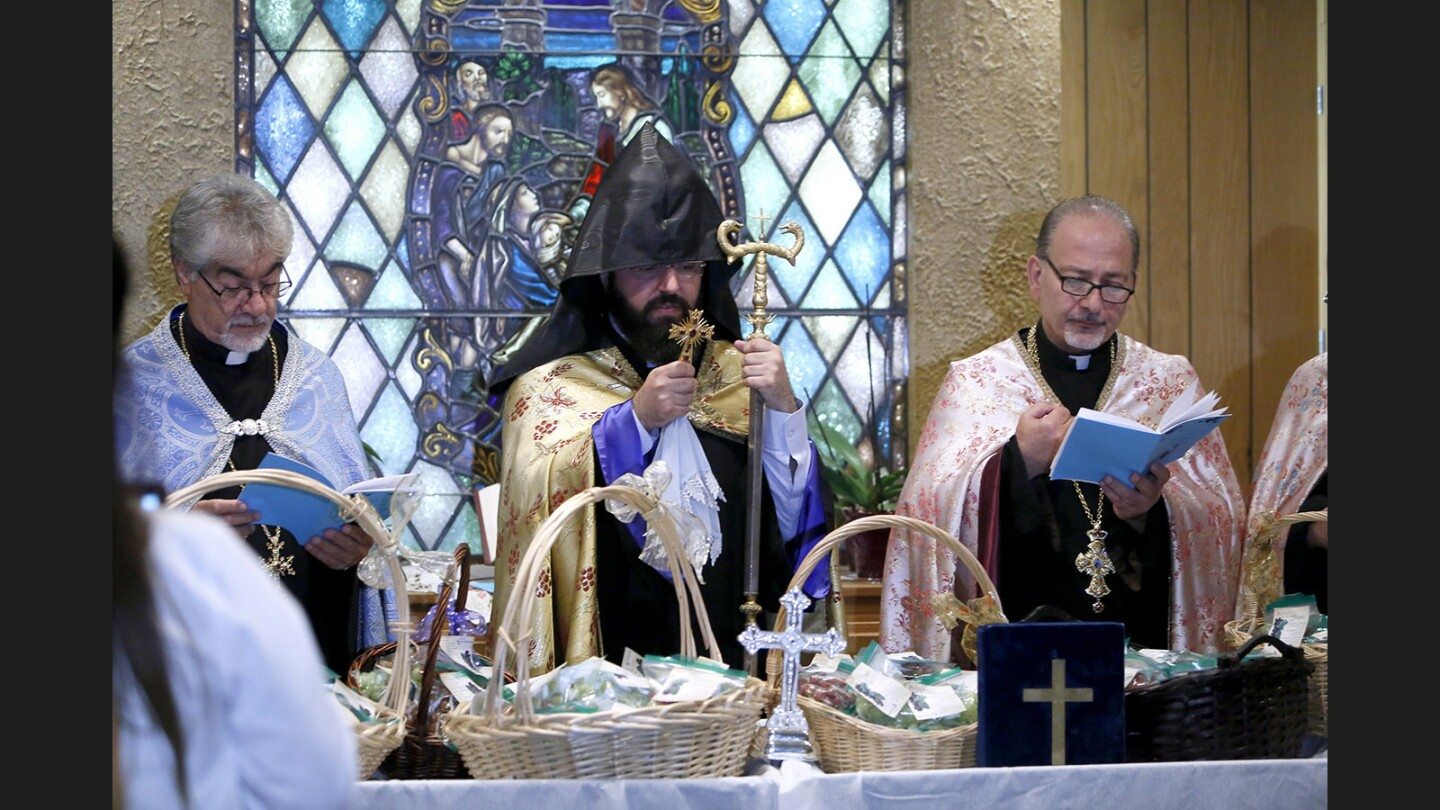 Left to right, Father Ardag, Father Torgom and Father Vazgen, from St. Mary's Armenian Apostolic Church, perform the Blessing of the Grapes service at Glendale Adventist Medical Center in Glendale on Wednesday, Aug. 9, 2017. Those in attendance received blessed grapes and some took additional bags of grapes for their patients and colleagues.
