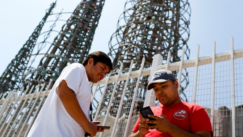 "Friends Franco, left, and Kyle play ""Pokemon Go"" at the Watts Towers."