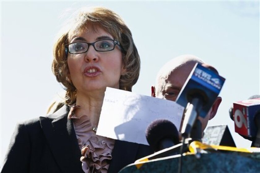 Former Rep. Gabrielle Giffords, left, reads a statement as she and husband Mark Kelly, right, returned to the site of a shooting that left her critically wounded to urge key senators to support expanded background checks for gun purchases, Wednesday, March 6, 2013, in Tucson, Ariz. (AP Photo/Ross D. Franklin)