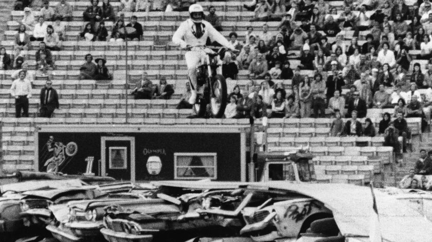 Evel Knievel leaps the smashed bodies of more than 50 cars, set 18 abreast, on his motorcycle in a stunt at the Coliseum on Feb. 18, 1973.