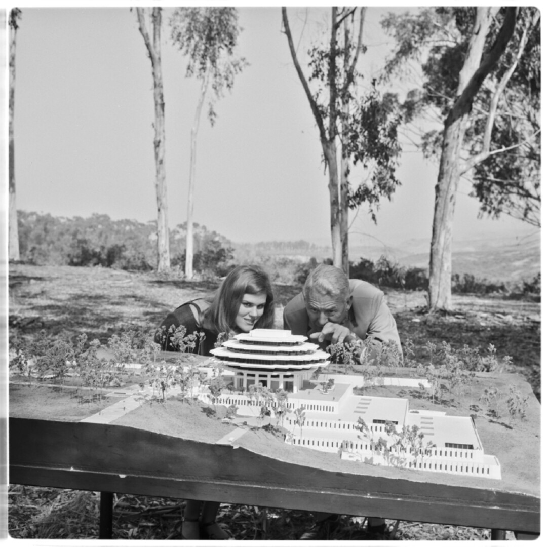 Freshman Valerie Lipiniski and Chancellor John S. Galbraith study model of UCSD's new Central Library in 1967.