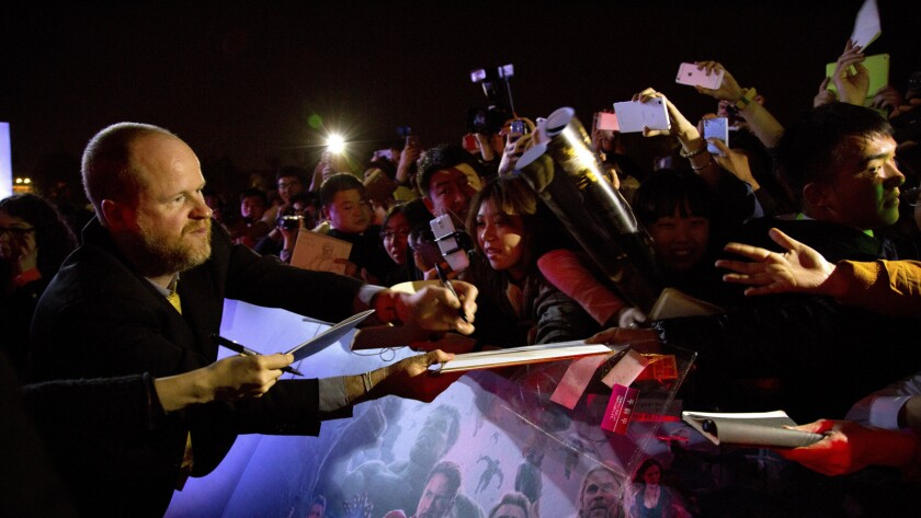 "Director Joss Whedon, left, signs autographs for Chinese fans at a red carpet event for his film, Marvel's ""Avengers: Age Of Ultron"" in Beijing."