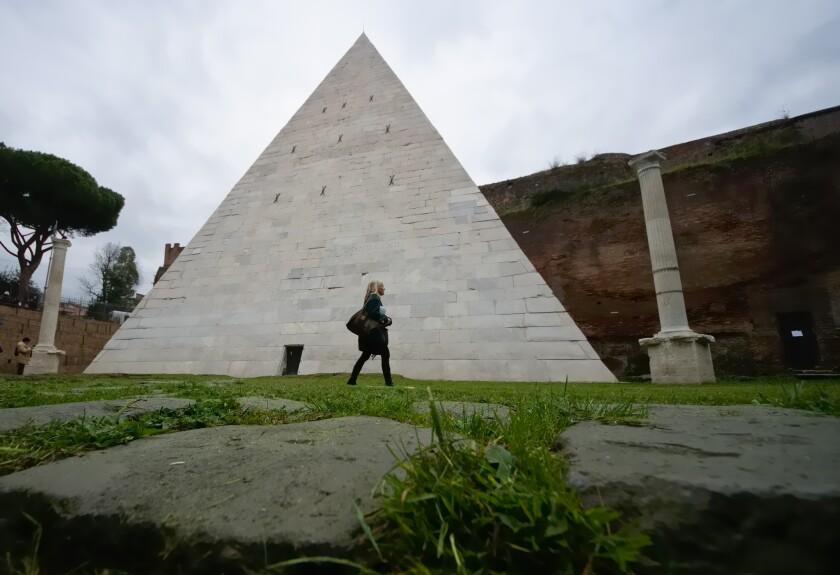 Una mujer camina frente a la Pirámide Cestia en Roma. La única pirámide sobreviviente de la antigüedad en Roma obtendrá nueva cara. Después de que un magnate de la industria textil japonés pagara la limpieza, los arqueólogos están ansiosos por presumir el monumento, construido hace unos 2.000 años como una tumba para enterrar al pretor romano, o magistrado, llamado Cayo Cestio. (Foto AP/Domenico Stinellis)