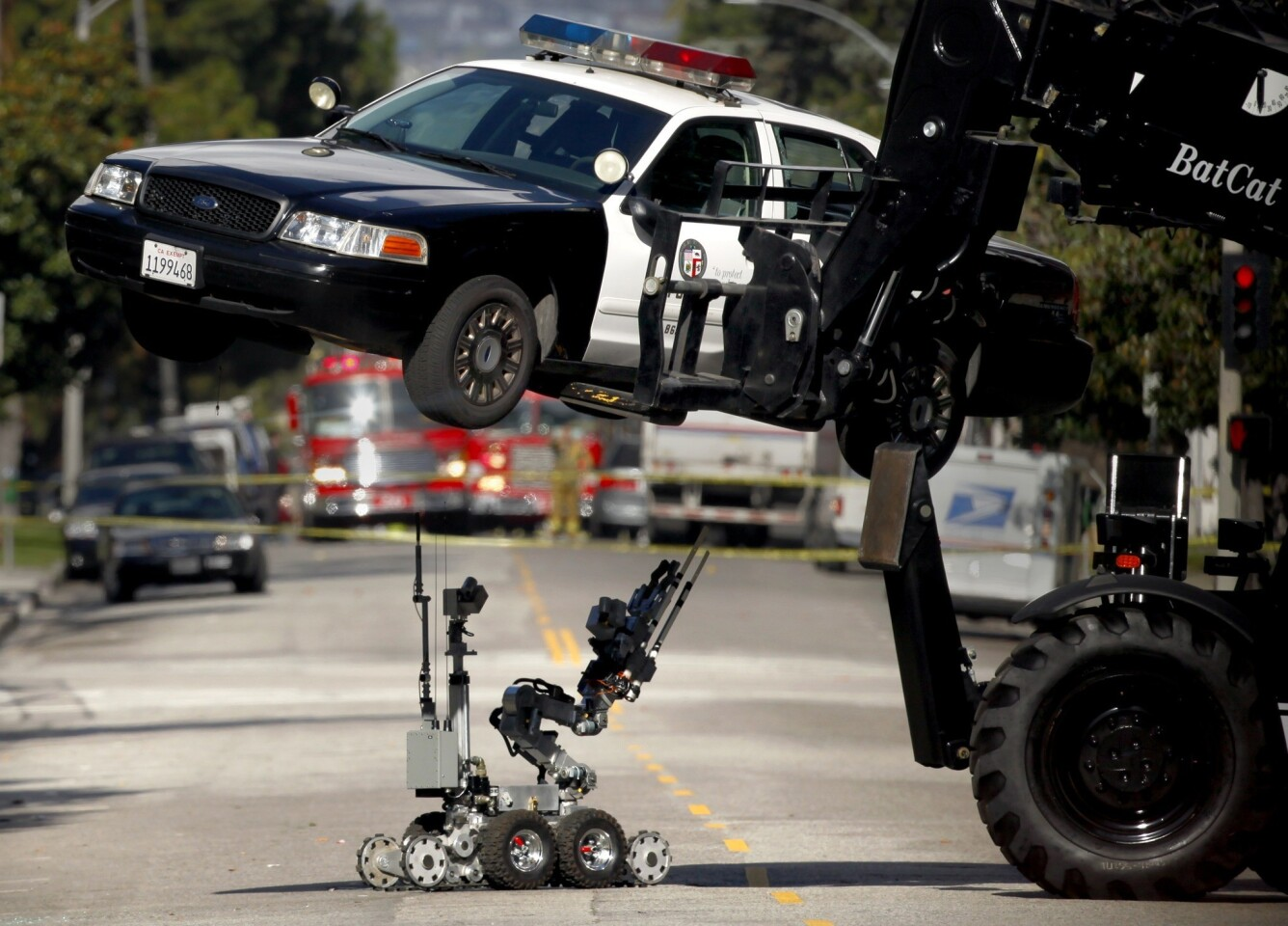 Los Angeles Police Department bomb squad members take a closer look at the underside of an LAPD patrol car with a robotic device after authorities received a call that a bomb had been planted in the vehicle on Harvard Boulevard near Wilshire Boulevard.