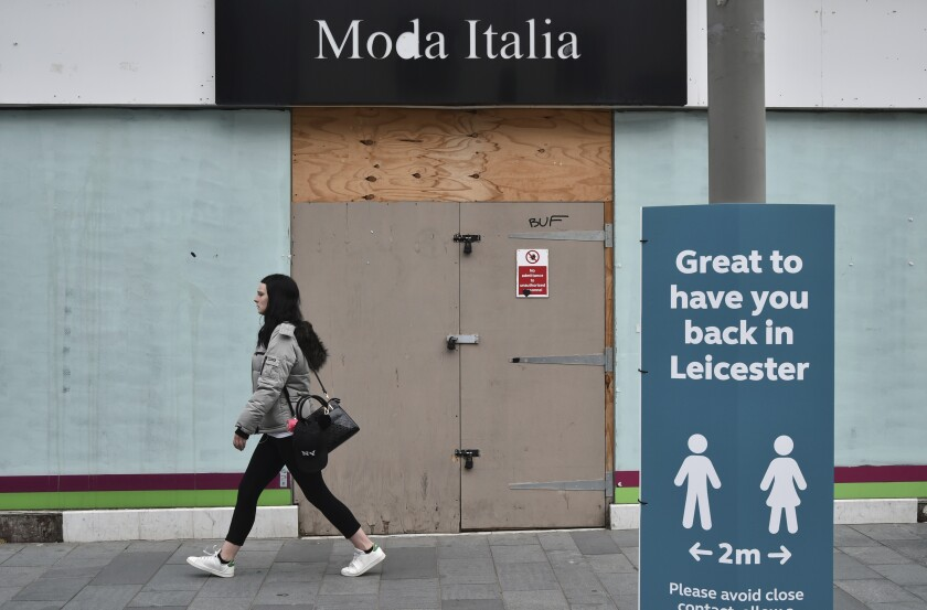 A woman walks past a boarded-up shop in Leicester, England