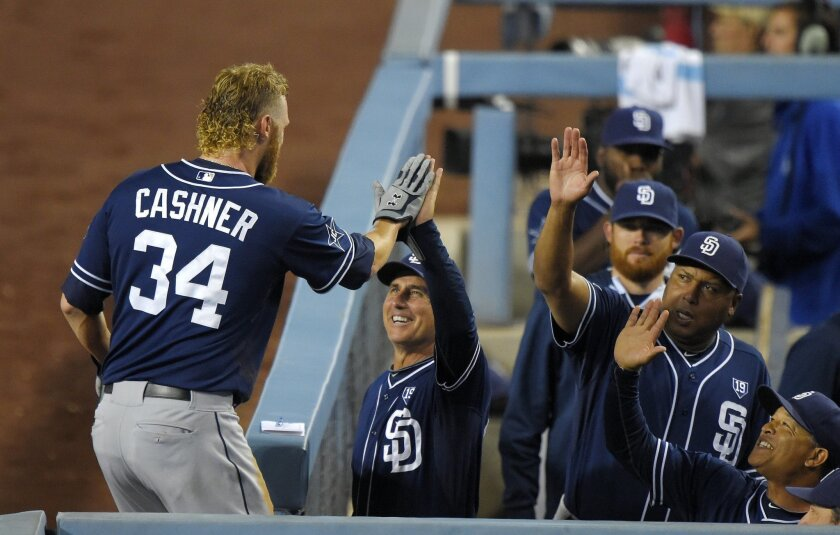 San Diego Padres' Andrew Cashner, left, is congratulated by San Diego Padres manager Bud Black, second from left, and other teammates after scoring on a single by Jeff Francoeur during the second inning of a baseball game, Tuesday, Sept. 9, 2014, in Los Angeles. (AP Photo/Mark J. Terrill)