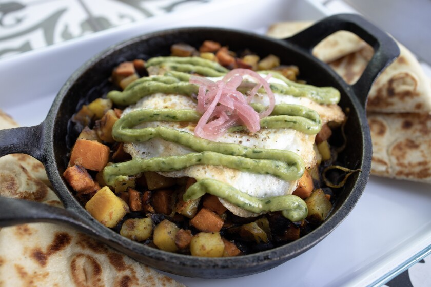 The Medina Breakfast Skillet is served in a cast iron pan with cubed sweet potatoes, black beans, caramelized onions, merguez sausage and topped with a fried egg and roasted jalapeno-avocado salsa.