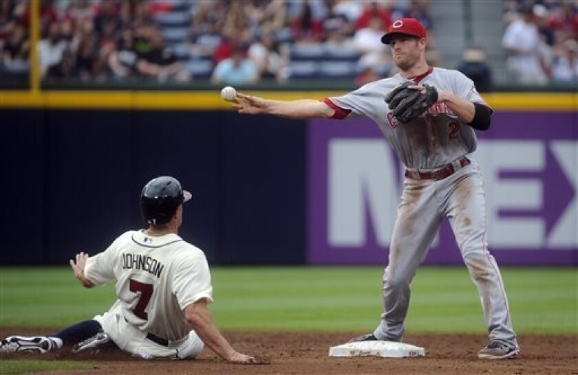 Cincinnati Reds shortstop Corky Miller (2) forces out Atlanta Braves' Reed Johnson (7) but cannot make the double play during the third inning of a baseball game on Saturday, July, 13, 2013, in Atlanta. Atlanta won 5-2. (AP Photo/John Amis)