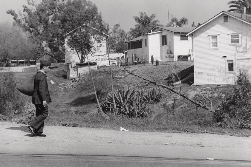 A black-and-white photograph shows a Mexican American soldier walking alone through a neighborhood