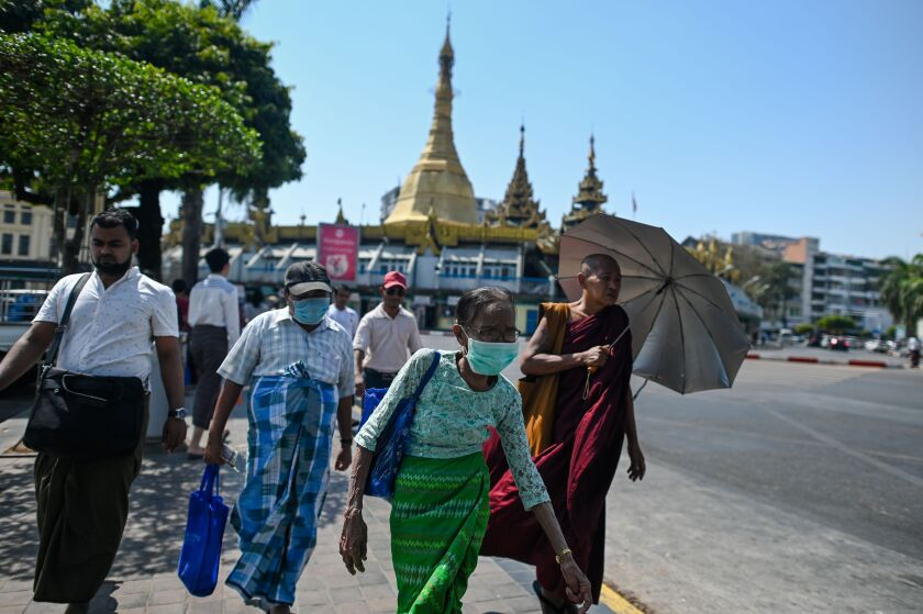 People wearing masks walk to a bus stop in Yangon, Myanmar.