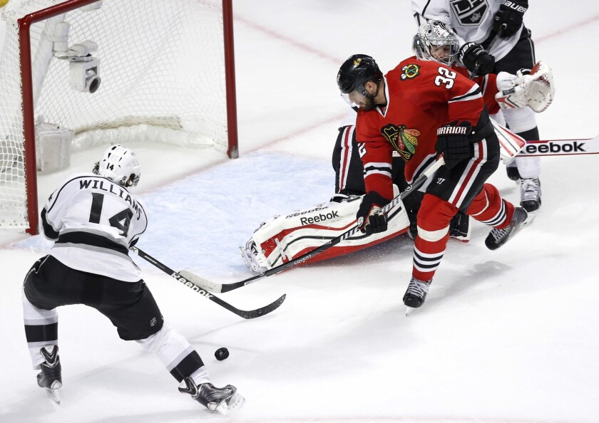 Blackhawks defenseman Michal Rozsival moves in to prevent Kings right wing Justin Williams from scoring into an open goal in the second period.