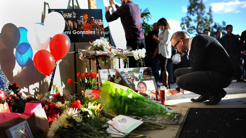Flowers and photos are left at a makeshift memorial for Nohemi Gonzalez outside of the design building at Cal State Long Beach.