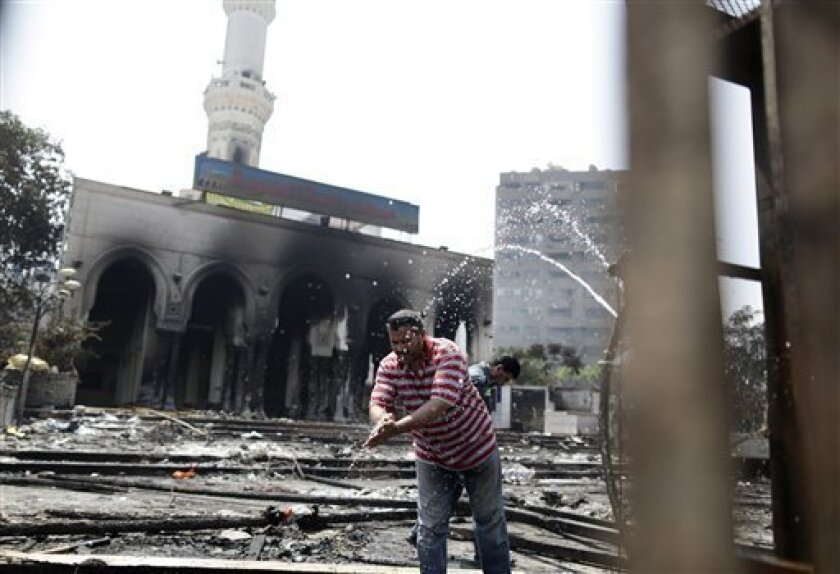 An Egyptian man cleans his hands outside the charred remains of the Rabaah al-Adawiya mosque, in the center of the largest protest camp of supporters of ousted President Mohammed Morsi, that was cleared by security forces, in the district of Nasr city, Cairo, Egypt, Thursday, Aug. 15, 2013. Egypt faced a new phase of uncertainty on Thursday after the bloodiest day since its Arab Spring began, with hundreds of people reported killed and thousands injured as police smashed two protest camps of sup