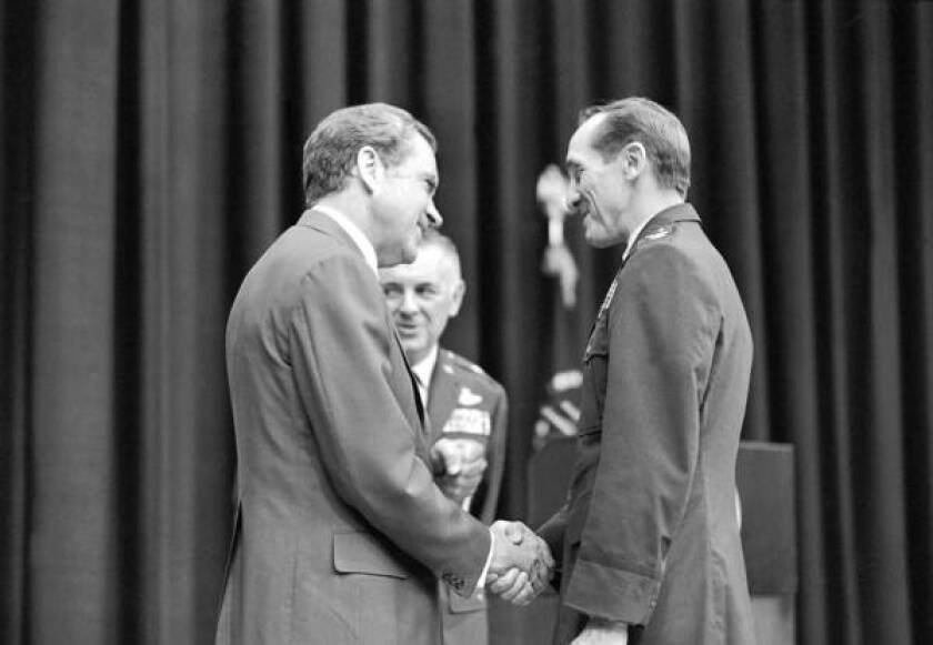 President Richard Nixon shakes hands with Col. J. Robinson Risner in 1973 as a group of former POWs visits Washington.