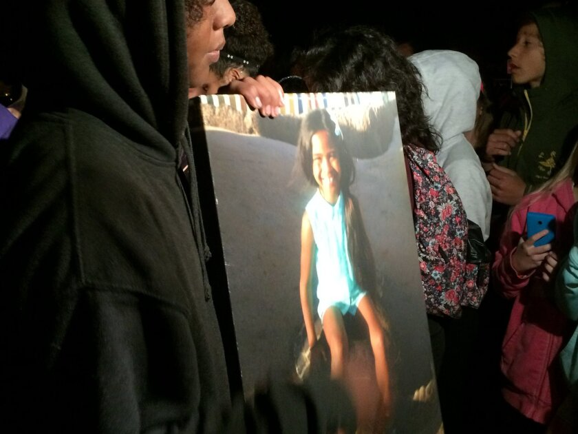 Lee Rosete, 13, holds a picture of his sister Raquele Rosete at a vigil Thursday at Orlek Park in Tierrasanta. The 10-year-old girl died after she was injured in a hit-and-run crash Sunday.