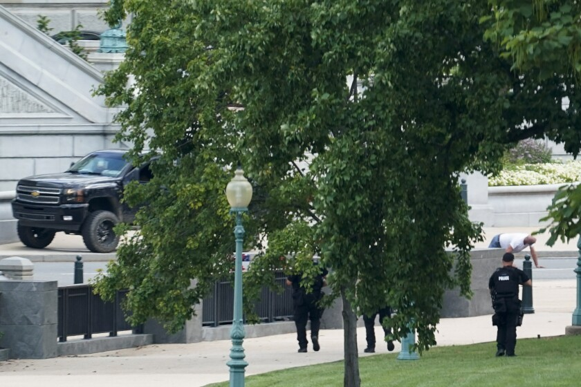 FILE - In this Aug. 19, 2021, file photo a person is apprehended after being in a pickup truck parked on the sidewalk in front of the Library of Congress' Thomas Jefferson Building, as seen from a window of the U.S. Capitol in Washington. The man who claimed he had a bomb in a pickup truck near the U.S. Capitol last month, prompting evacuations and an hourslong standoff with police, is competent to stand trial, a federal judge ruled Wednesday, Sept. 22. Floyd Ray Roseberry pleaded not guilty in federal court Wednesday to charges that include threatening to use a weapon of mass destruction. (AP Photo/Alex Brandon, File)