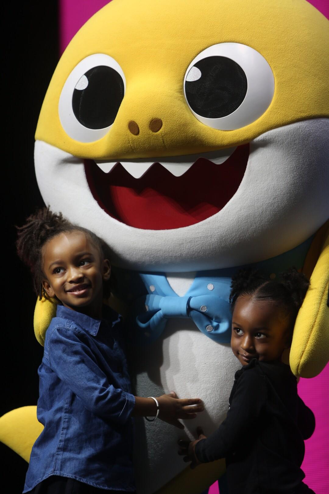 Anaiah, left, and Zariah Lafond get a baby shark hug