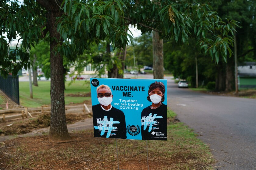 """A roadside sign beneath trees, says """"Vaccinate me. Together we are beating COVID-19."""""""