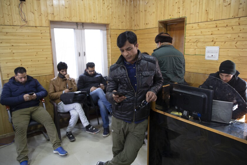 FILE - In this Jan. 30, 2020, file photo, Kashmiri journalists browse the internet on their mobile phones inside the media center set up by government authorities in Srinagar, Indian controlled Kashmir. Indian authorities on Wednesday, March 4, temporarily revoked a ban on social media sites and restored full internet access in disputed Kashmir for two weeks, seven months after they stripped the restive region of its statehood and semi-autonomy and enforced a total communications blackout. (AP Photo/Dar Yasin, File)