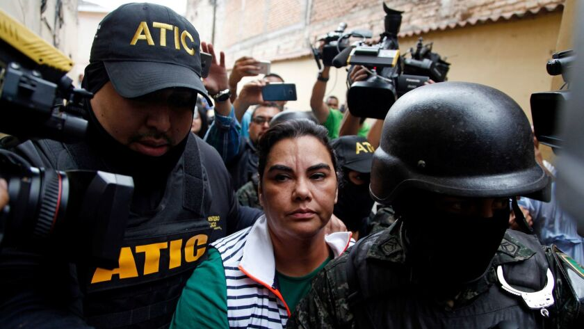Police escort Honduras' former first lady Rosa Elena Bonilla away from a police station, surrounded