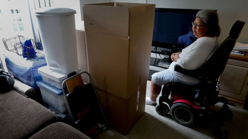 JoAnn Hesson, 68, sits among her moving boxes and personal belongings in her apartment in Rancho Santa Margarita. Hesson took out several high-interest installment loans in 2015 and is considering filing for bankruptcy. She has since moved to Phoenix to be closer to family.
