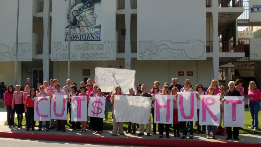 La Ca–ada's teachers and school supporters stand in front of the school, holding signs in demonstrat