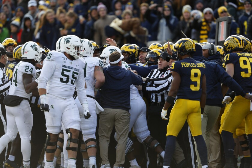 Officials separate Michigan State and Michigan players during a scuffle in the second half of a game Nov. 16.