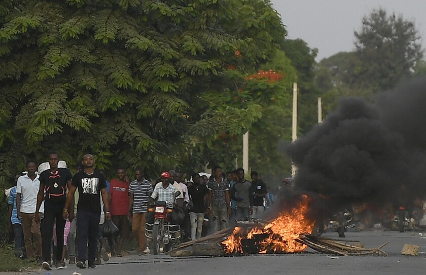 Varios hombres caminan junto a una barricada en llamas después de que cientos de trabajadores huyeran de una zona en la que se llevaron a cabo manifestaciones que se tornaron violentas cerca de la ciudad natal del difunto presidente Jovenel Moïse, el miércoles 21 de julio de 2021, en Quartier Morin, un distrito de Cap Haitien, en el norte de Haití. (AP Foto/Matías Delacroix)