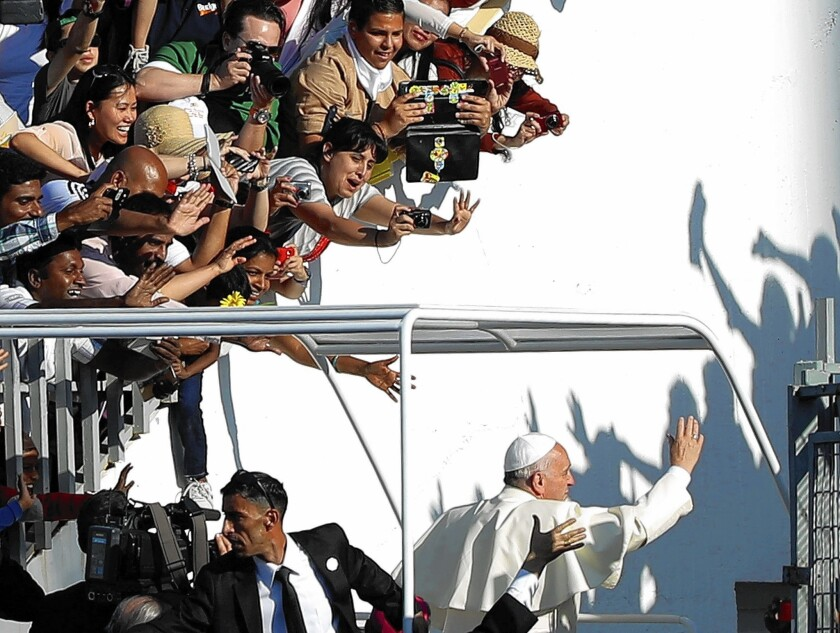 Pope Francis greets the crowd as he leaves a stadium Mass in Amman, Jordan, on the first day of a three-day visit to the Middle East.