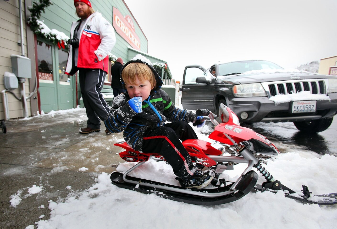 Grady Ebert, 5, traveled with his father Chris Ebert, rear, and the rest of his family from El Cajon to Julian for an old-fashioned snow day in the mountains.  Here they stopped on Main Street in Julian and Grady tried out the taste of fresh snow.