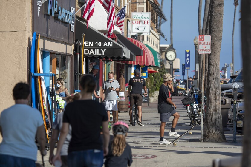 People walk and skateboard on the sidewalk past businesses on West Oceanfront in Newport Beach.