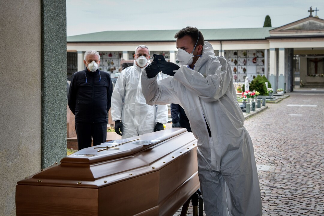 A pallbearer photographs a coffin for relatives of the deceased at a cemetery in Italy.
