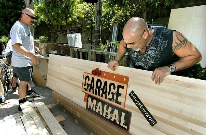 "Bill Goldberg, right, and carpenter Steve VanDuzen move a large wooden panel with the ""Garage Mahal"" TV show's logo. The wood panel is featured in the show at Golberg's Bonsall home where his garage is being made over."