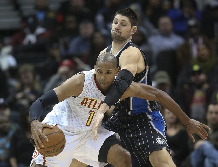 Atlanta Hawks center Al Horford, left, is defended by Orlando Magic center Nikola Vucevic, right, in the second half of an NBA basketball game Monday, Feb. 8, 2016, in Atlanta. Orlando won 117-110 in overtime. (AP Photo/John Bazemore)