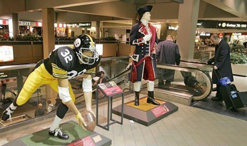 A pair of heroes – George Washington and Steelers legend Franco Harris – greet passengers at Pittsburgh's airport. (Sean M. Haffey / Union-Tribune)