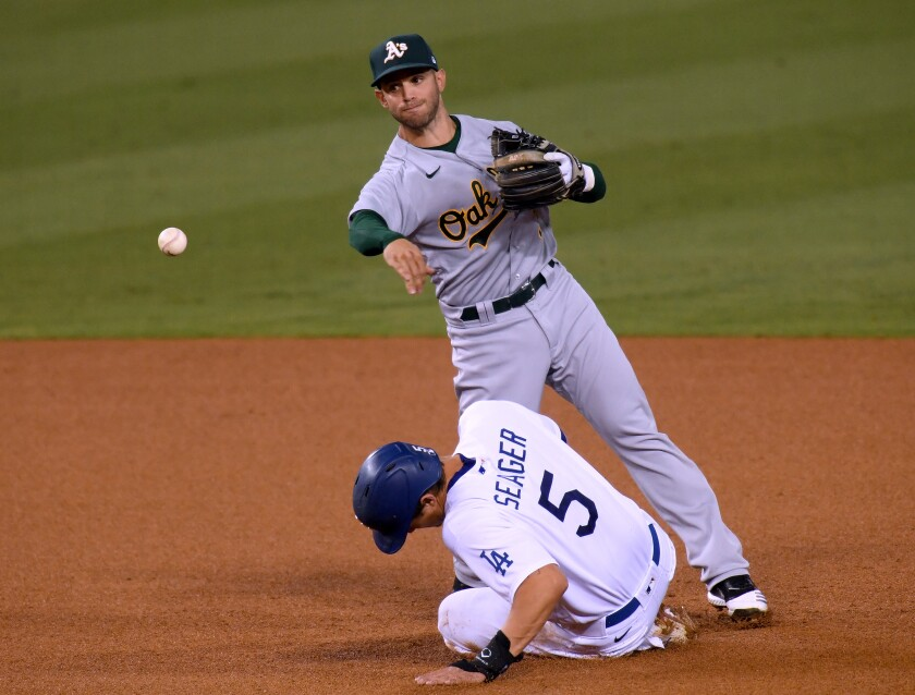 Tommy La Stella #3 of the Oakland Athletics attempts a throw over Corey Seager.